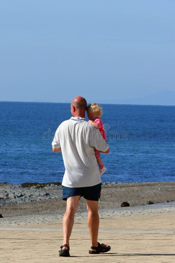 In Daddys Arms. Father with his young blonde haired daughter in his arms, strolling along a beach promenade with the sea in the distance stock photography