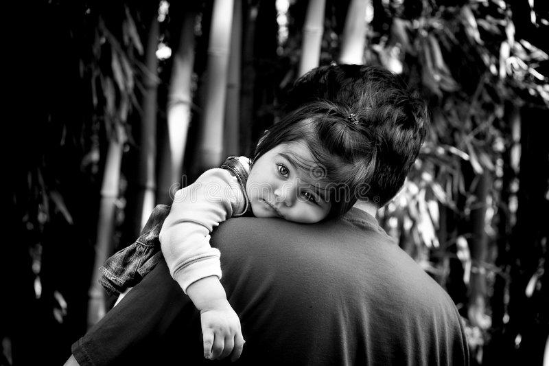 Daddys girl. Tired baby in her dady's arms stock photography