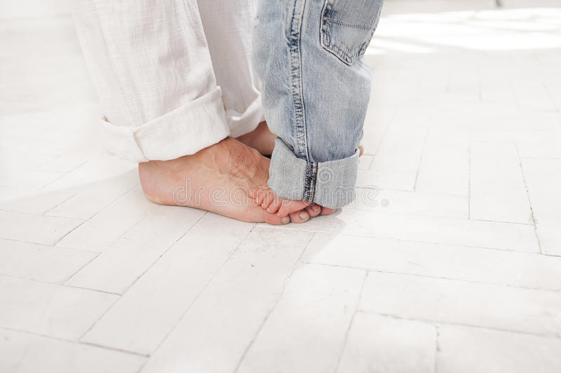 The daddys and his nine months old son feet. Small and big on white home background stock photo
