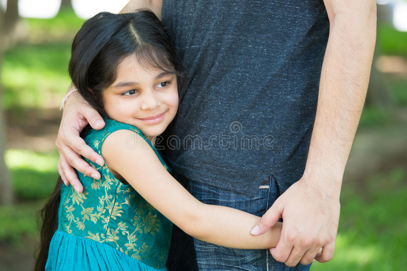 Daddys little girl. Closeup portrait, young child hugging her father tenderly, outdoors outside green grass background. Daddy's little girl royalty free stock photos
