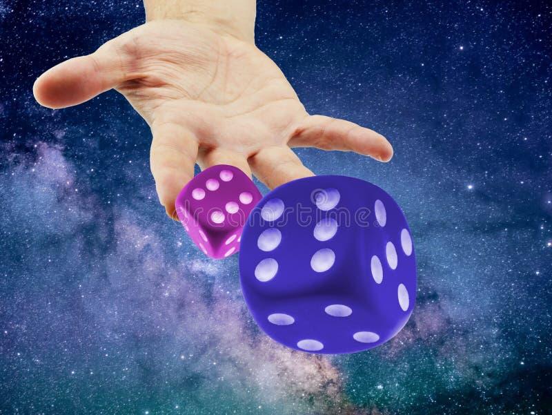 Dadi di lancio o di rotolamento della mano nel cosmo o nell'universo Concetto di casualità o di causalità fotografie stock libere da diritti