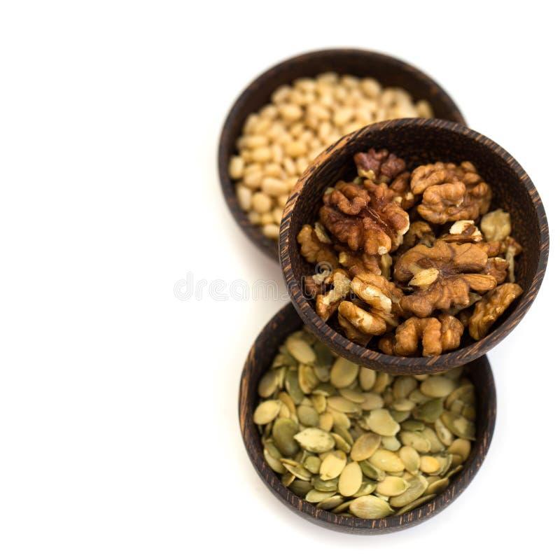 Dadi e semi di zucca in una ciotola di legno immagini stock