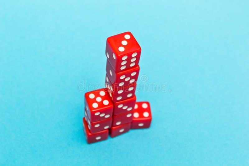 Dadi rossi sotto forma di una piramide, coltivante uno - sei, su un fondo blu fotografia stock libera da diritti