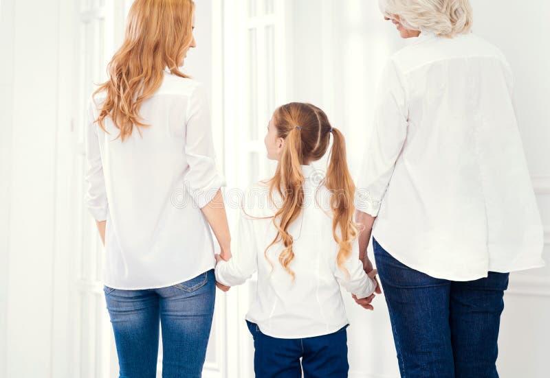 Dado vuelta detrás tres generaciones de mujeres que llevan a cabo sus manos juntas imagenes de archivo