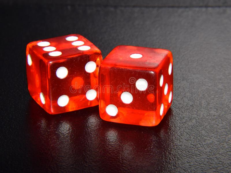 Dados de juego del casino rojo original en fondo reflector texturizado negro fotografía de archivo