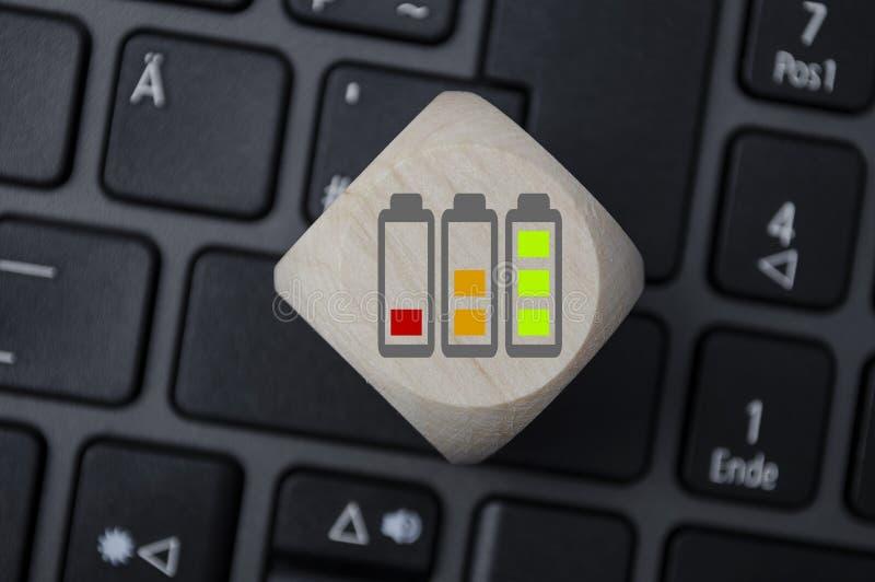 Dados del cubo con símbolos del cargamento de la batería imagen de archivo