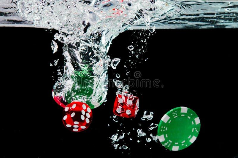 Dados e microplaquetas vermelhos na água no fundo preto fotos de stock royalty free