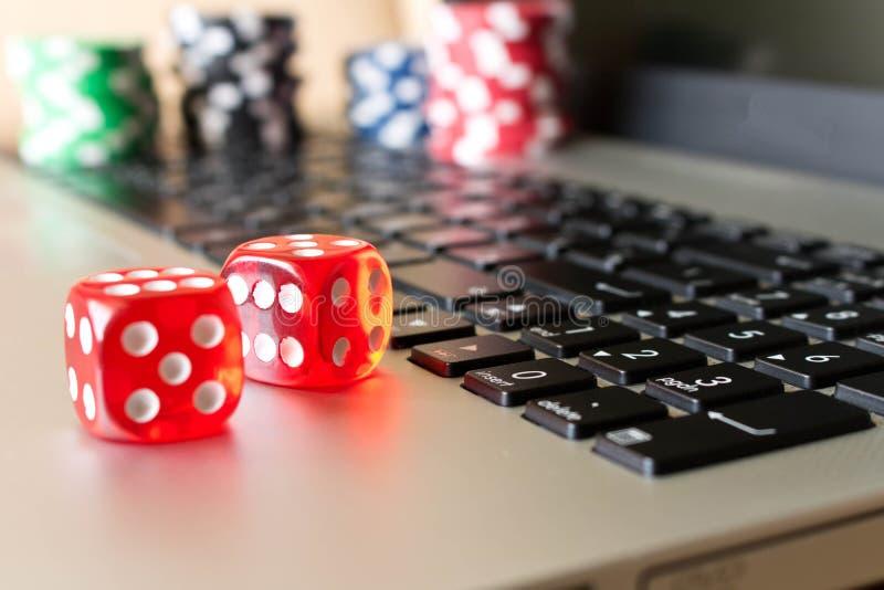 Dados, fichas de póker en el ordenador portátil El concepto de juegos onlines Cl imágenes de archivo libres de regalías