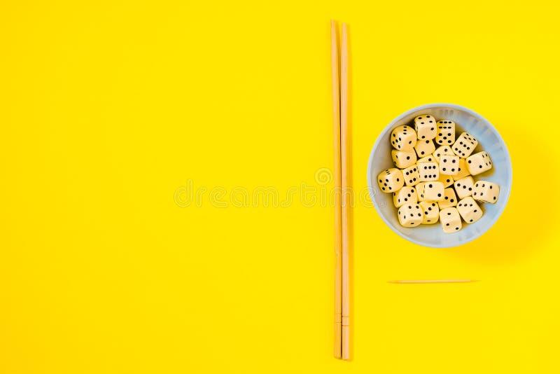 Dados na bacia branca com os hashis no fundo amarelo foto de stock royalty free