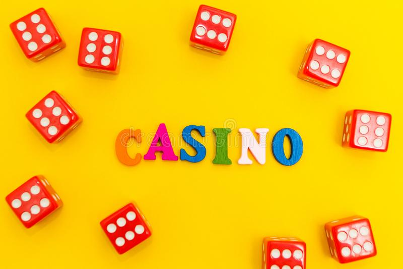 Dados vermelhos com sixes em um fundo amarelo, inscrição do casino foto de stock