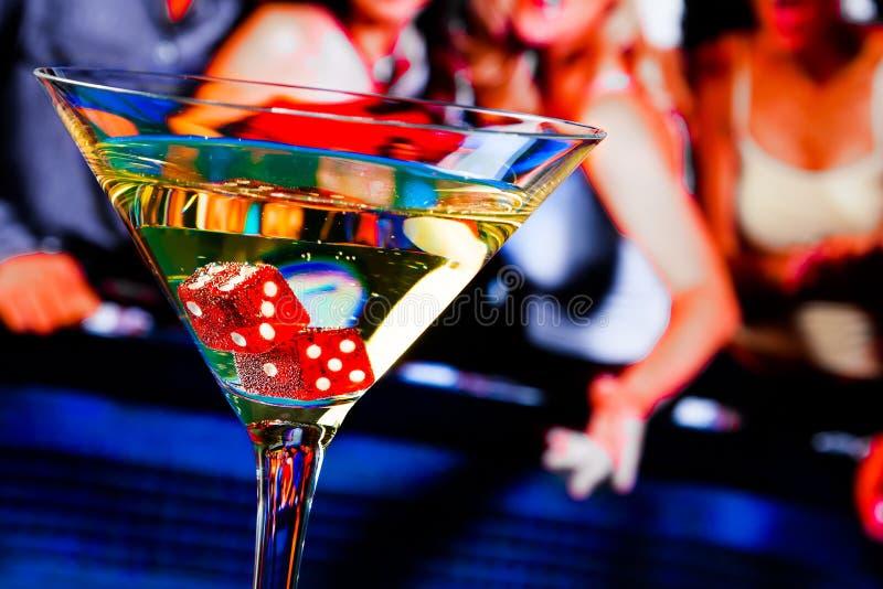 Dados vermelhos no vidro de cocktail na frente da tabela de jogo imagens de stock