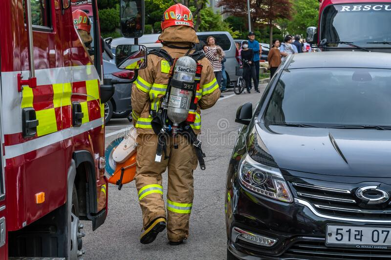 Firefighter in full gear. Daejeon, South Korea; May 2, 2020: Firefighter in full gear walks in front of fire truck after helping to contain fire at Hanshin stock photo
