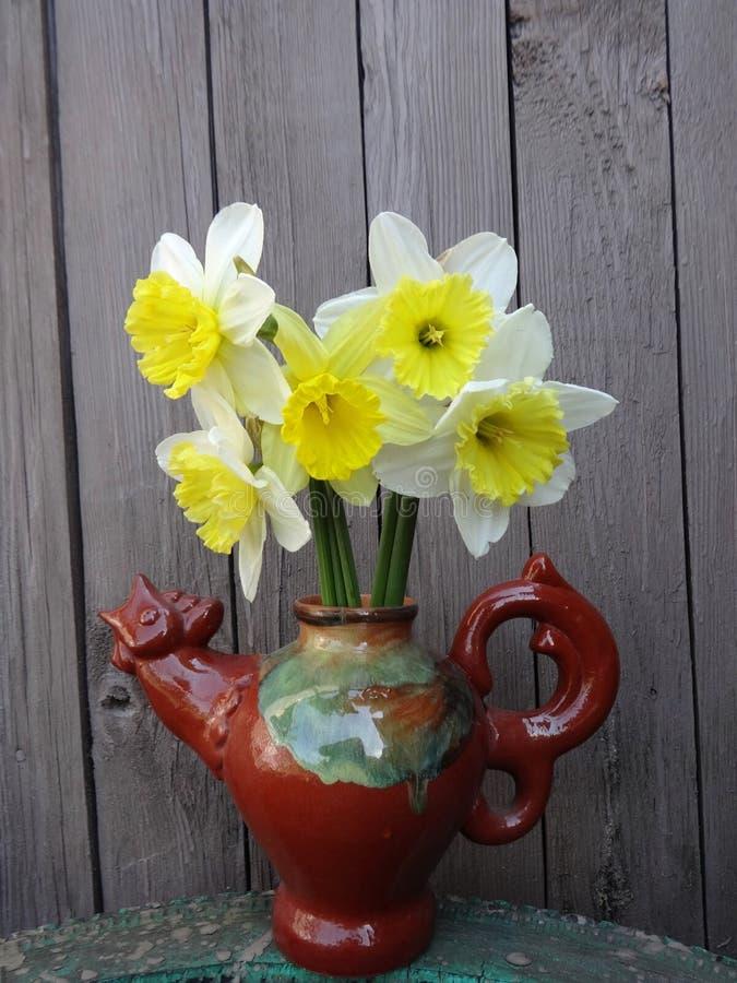 daffodils в вазе на деревянной предпосылке стоковая фотография rf