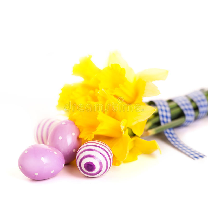 Daffodils and easter eggs on white. Background royalty free stock photo