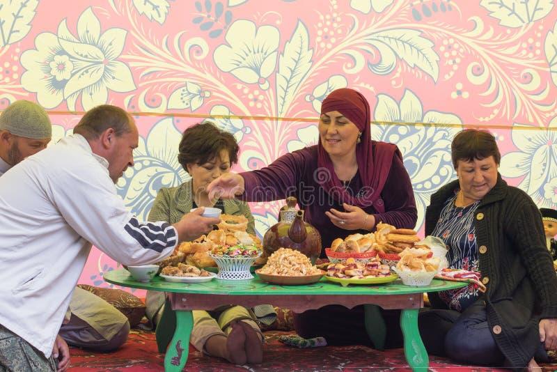 Dag av den Tatar byn av nya Yurts Folket sitter i ett tält på en traditionell låg tabell fotografering för bildbyråer