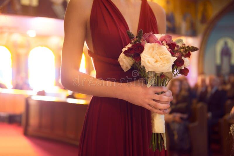 Dag för bröllopceremoni brudtärnaflickan som bär det eleganta röda klänninginnehavet, blommar buketten på bröllopceremoni i katol royaltyfria bilder