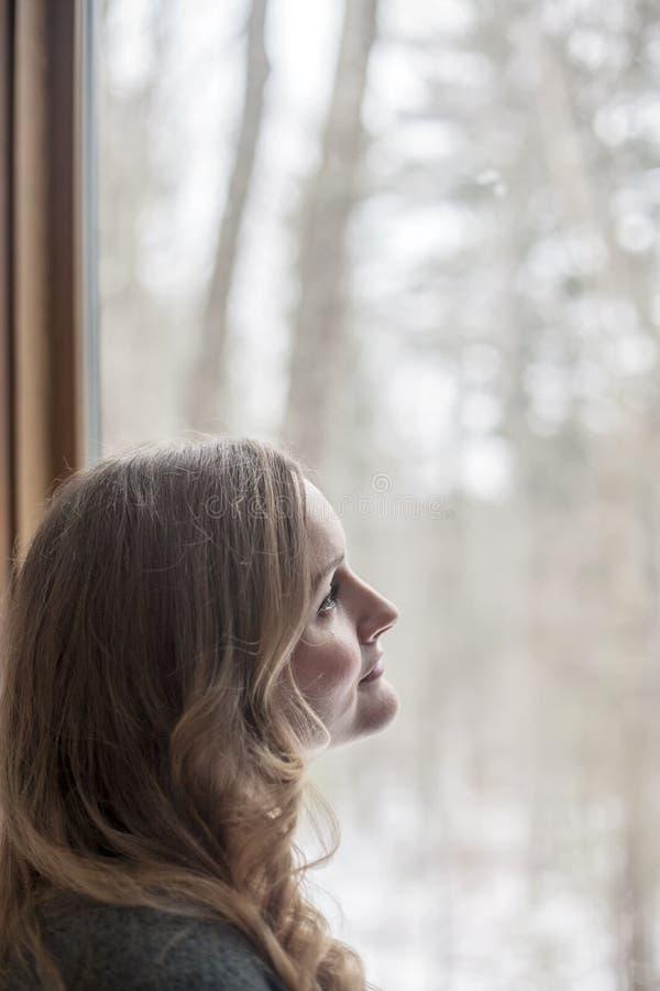 Dag för ung kvinna som ut drömmer och ser fönstret royaltyfri foto