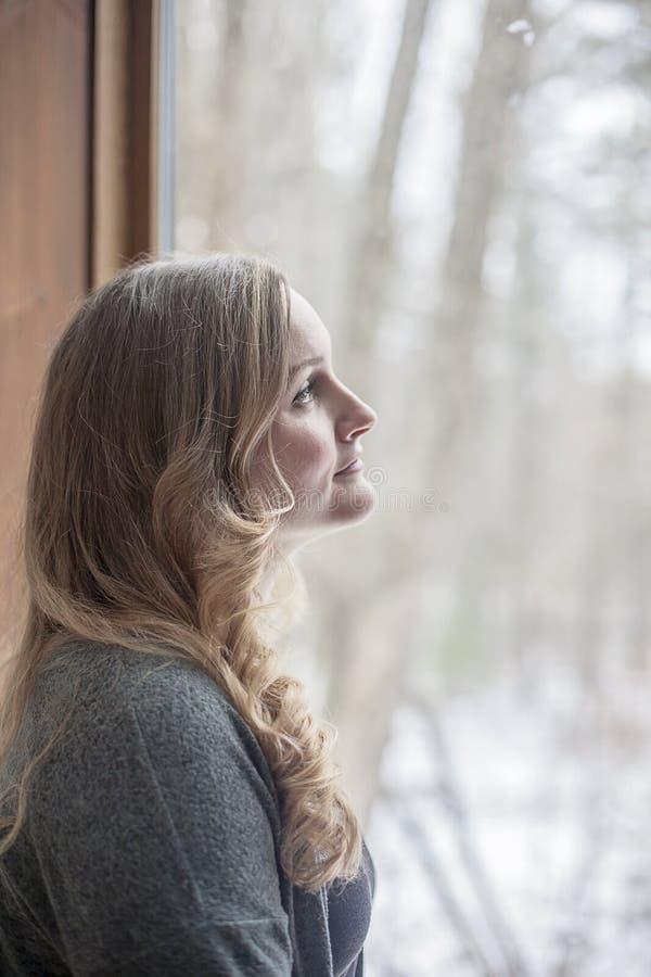 Dag för ung kvinna som ut drömmer och ser fönstret arkivbilder