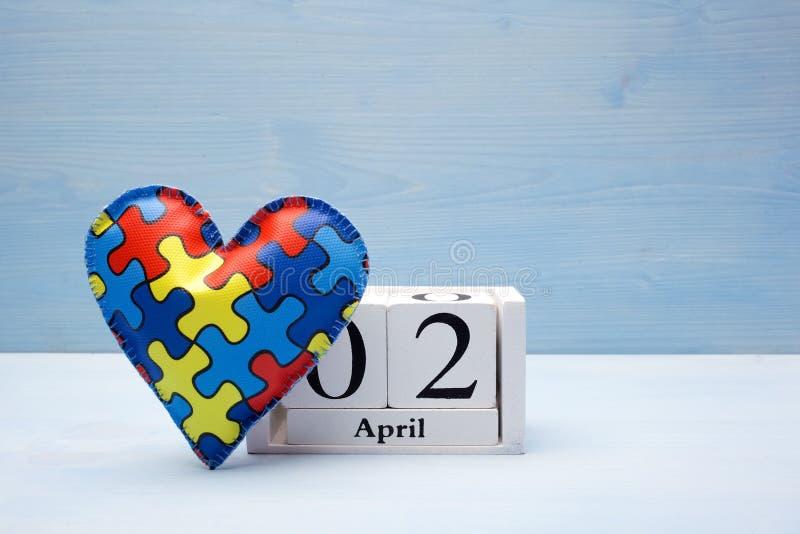 Dag för världsautismmedvetenhet, mentalt hälsovårdbegrepp med pusslet eller figursågmodell på hjärta med kalendern arkivbild