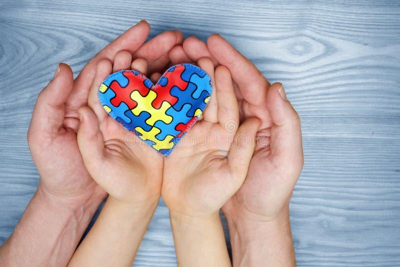 Dag för världsautismmedvetenhet, pussel eller figursågmodell på hjärta med autistiska barns och faderhänder arkivfoton