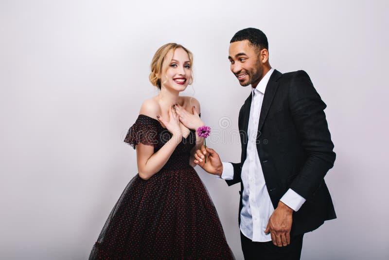 Dag för valentin s för lyckliga gulliga par förälskad fira på vit bakgrund Attraktiv ung blond kvinna i lyxig klänning royaltyfria foton