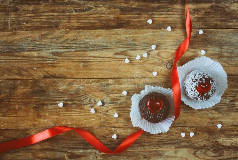 Dag för valentin` s, två söta kakor, hjärtor, scharlakansrött siden- band arkivbild