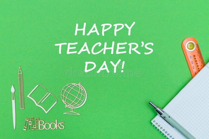 Dag van de tekst levert de gelukkige leraar ` s, school houten miniaturen, notitieboekje op groene achtergrond royalty-vrije stock foto