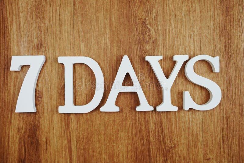7 dagar alfabetbokstav med utrymmekopian på träbakgrund royaltyfri foto