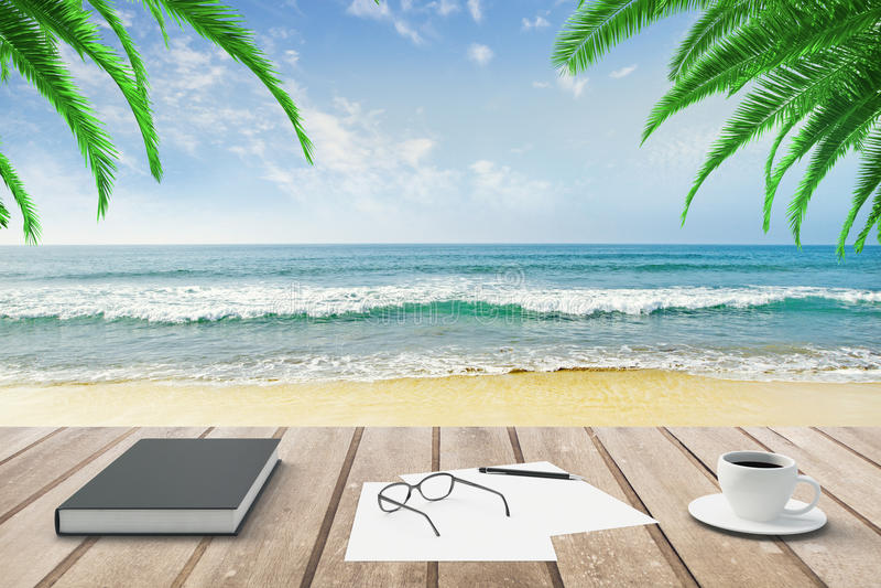 Dagbok, tom legitimationshandlingar och kopp kaffe på träbänk på strand b arkivbild