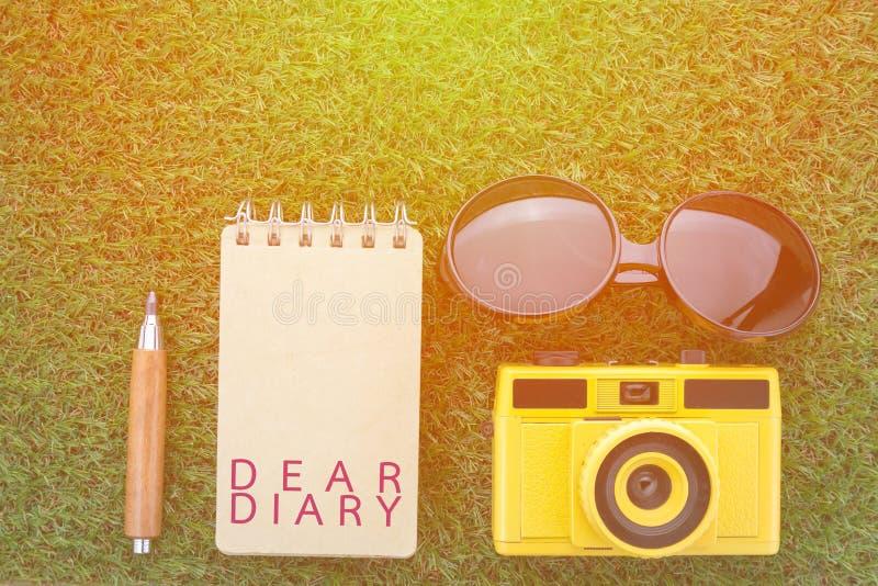 Dagbokbegrepp med kameran för anteckningsbok för solexponeringsglas och den skarpa blyertspennan royaltyfri bild