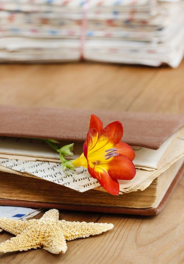 Dagboken, gamla bokstäver och röd freesia blommar royaltyfria foton