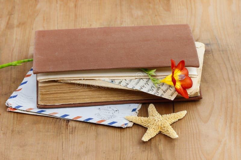 Dagboken, gamla bokstäver och röd freesia blommar arkivfoto