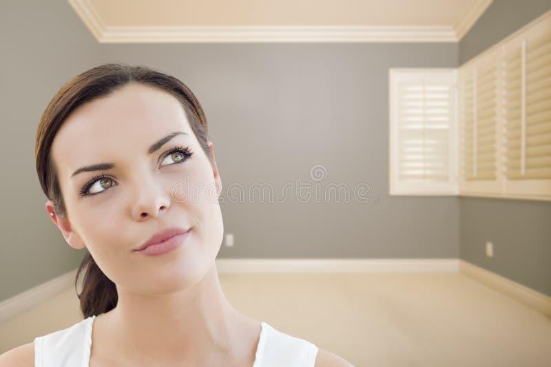 Dagdrömma den unga kvinnan i tomma Grey Room arkivbild
