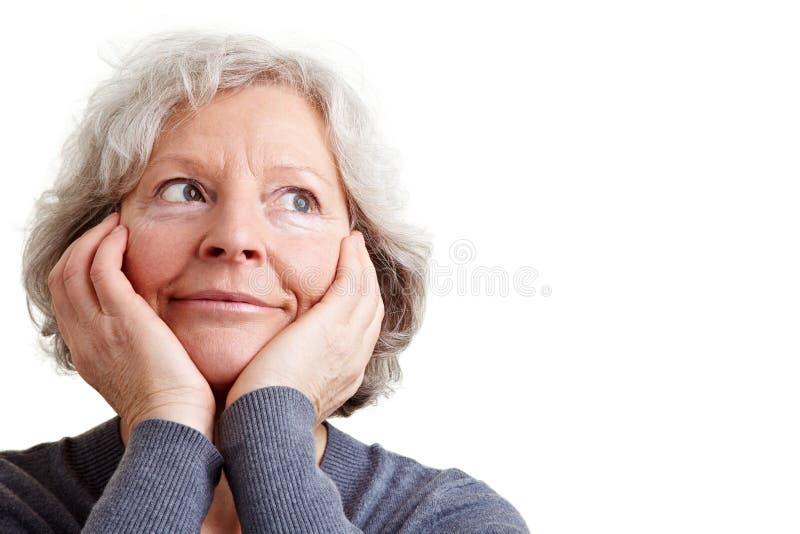 dagdrömma gammalare kvinna royaltyfria bilder
