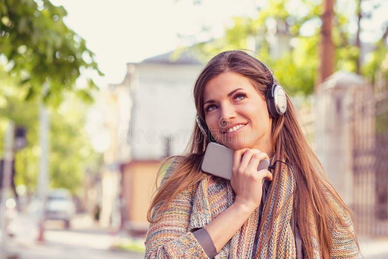 Dagdrömma kvinnan som lyssnar till musiken på en smart telefon som går ner gatan på en solig dag för höst royaltyfri bild