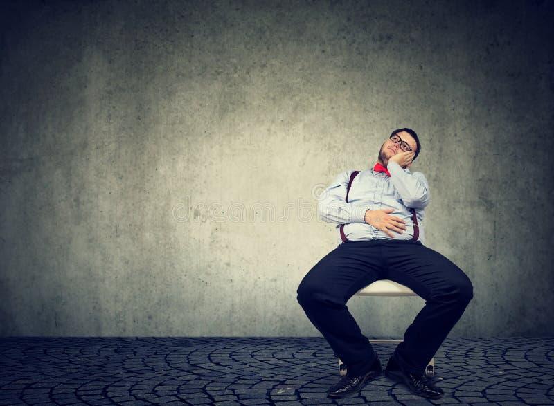 Dagdrömma sjukligt feta mannen som den är lat arkivbild