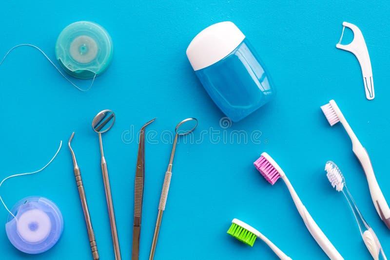 Dagelijkse mondelinge hygiëne voor familie Tandenborstel, tandzijde en tandartsinstrumenten op blauwe hoogste mening als achtergr stock afbeeldingen
