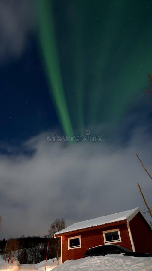 Dageraad - noordelijk licht recht boven de kleine hut stock afbeeldingen