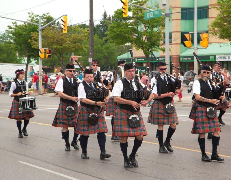 DAGERAAD, ONTARIO, CANADA 1 JULI: Ieren die in hun kilt hun doedelzak spelen tijdens de de Dagparade van Canada stock afbeelding