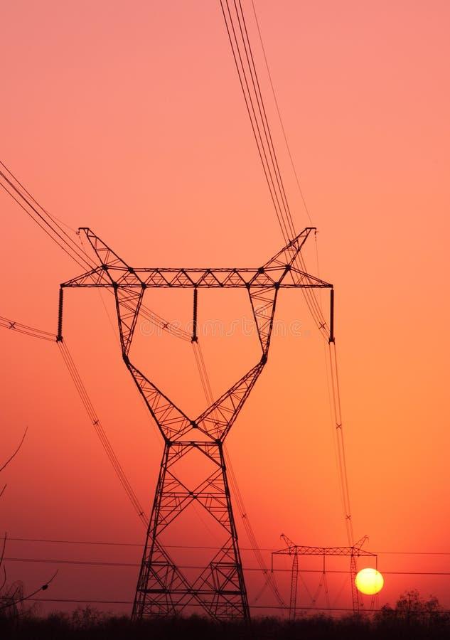 Dageraad van toren met hoog voltage stock afbeelding