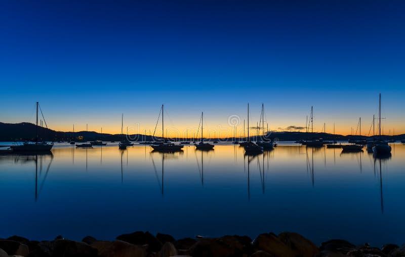 Dageraad waterscape over de baai met boten stock fotografie