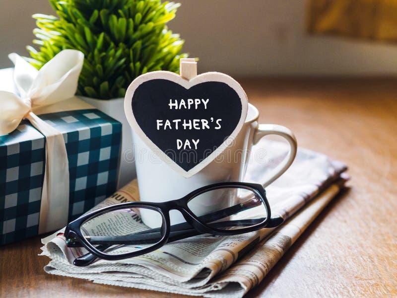 dagfader lyckligt s kaffekopp med gåvaasken, hjärtaetikett w royaltyfri bild