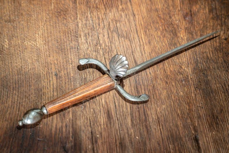 Dagger Ancient y viejo en fondo de madera imagen de archivo libre de regalías
