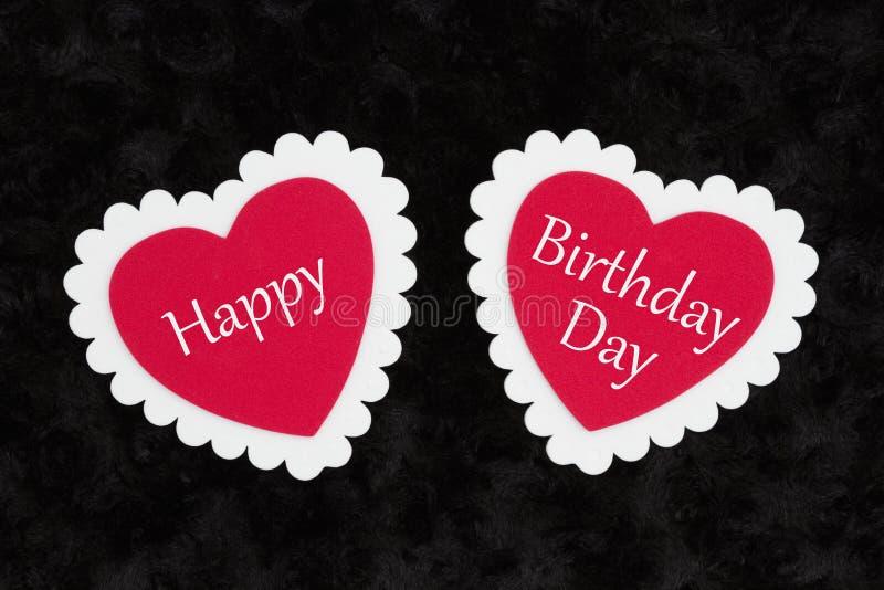 Daghälsning för lycklig födelsedag med vita och röda hjärtor på svart royaltyfri foto