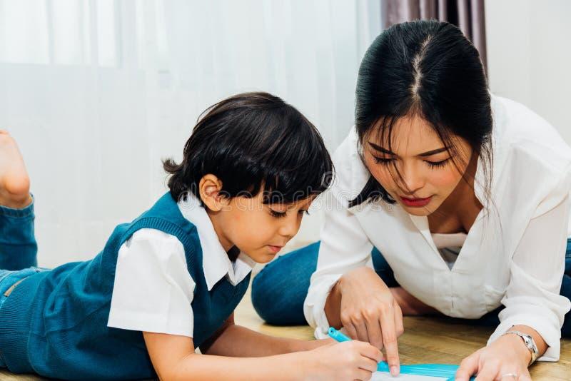 Dagis för son för pojke för familjbarnunge och härlig teckning för moderutbildningsundervisning tillsammans arkivfoto