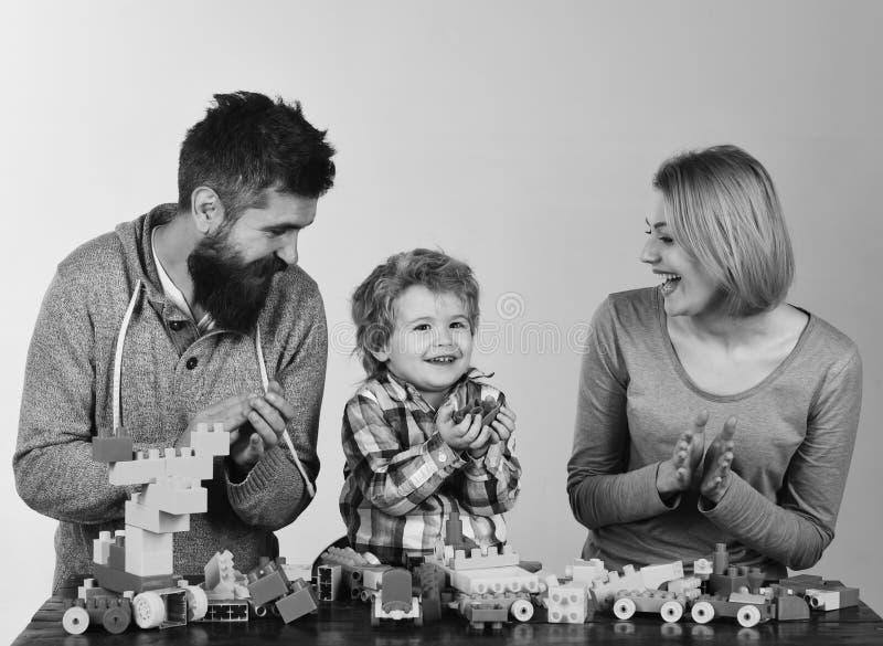 Dagis- och familjbegrepp Föräldrar och unge i lekrum Familj med upphetsat framsidabyggande ut ur kulört arkivbilder