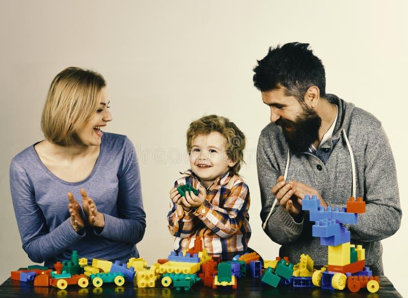 Dagis- och familjbegrepp Föräldrar och unge i lekrum Familj med upphetsat framsidabyggande ut ur kulört arkivbild