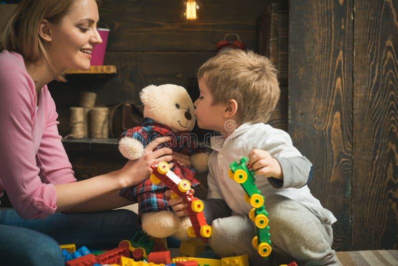 Dagisbegrepp Det lilla barnet och kvinnan spelar med leksaker i dagis Moder och son i dagis Välkomnande till… (Adobeillustratören arkivfoto