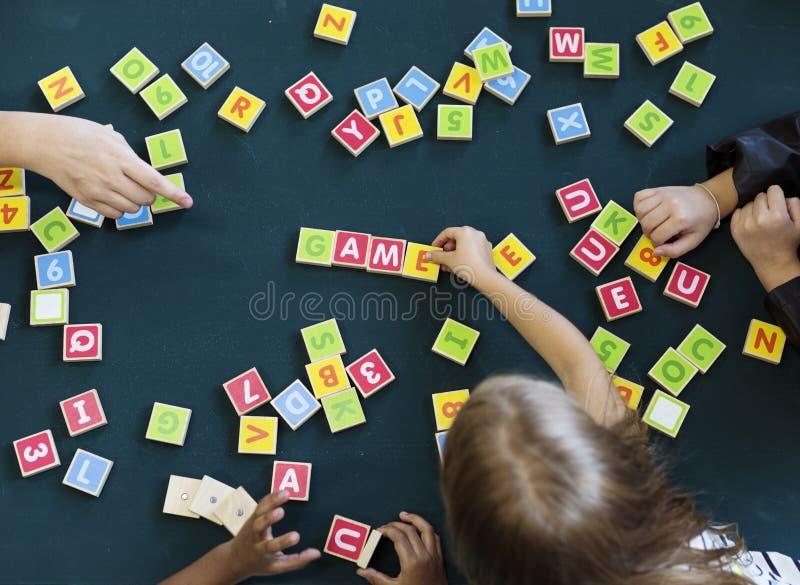 Dagisungar som spelar träalfabet, märker ordlistagummin royaltyfria bilder