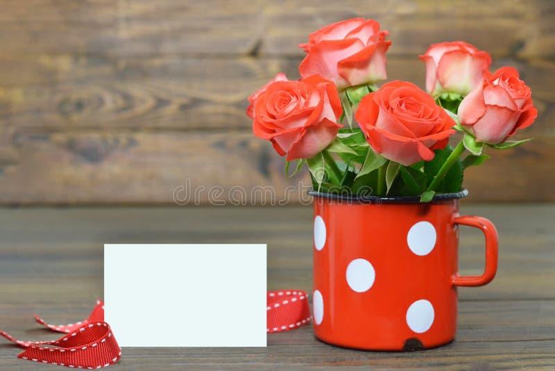 Dagkort med röda rosor i tappningkopp fotografering för bildbyråer